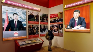 In this Oct. 23, 2017 photo, a man looks at pictures of Chinese President Xi Jinping at an exhibition highlighting China's achievements under five years of his leadership at the Beijing Exhibition Hall in the capital city where the 19th Party Congress is held. (AP Photo/Andy Wong)