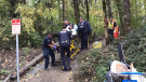 Police and paramedics escort a 72-year-old woman out of a Chilliwack homeless camp on a stretcher. Oct. 23, 2017.