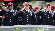 Members of the 3rd Special Forces Group Airborne 2nd Battalion leave pins and salute the casket after the burial of Army Sgt. La David Johnson at the Hollywood Memorial Gardens in Hollywood, Fla., on Saturday, Oct. 21, 2017. Sgt. Johnson was killed with three other colleagues in an ambush by extremists in Niger on Oct. 4. (Mike Stocker/South Florida Sun-Sentinel via AP)