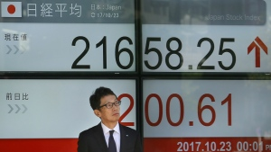 A man stands near an electronic stock indicator of a securities firm in Tokyo, Monday, Oct. 23, 2017. (AP / Shizuo Kambayashi)