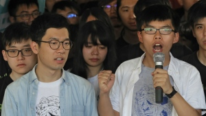 Hong Kong activist Joshua Wong, right, and Nathan Law, left, speak outside the high court before a ruling on a prosecution request for stiffer sentences following a lower court decision that let them avoid prison in Hong Kong on Aug. 17, 2017. (AP / Vincent Yu)