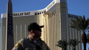 FILE - In this Oct. 3, 2017, file photo, a Las Vegas police officer stands by a blocked off area near the Mandalay Bay casino in Las Vegas. (AP Photo/John Locher, File)