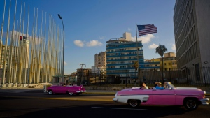 Tourists ride in classic American convertible cars past the United States embassy, right, in Havana, Cuba on Jan. 12, 2017. (AP / Ramon Espinosa)