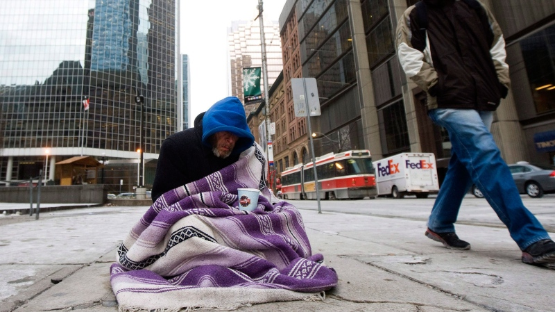 In this file photo, a homeless person panhandles for money in Toronto on Monday, Dec. 13, 2010. (The Canadian Press / Nathan Denette)
