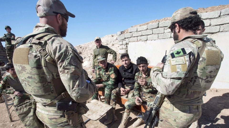 Canadian special forces soldiers, left and right, speak with Peshmerga fighters at an observation post, Monday, February 20, 2017 in northern Iraq. THE CANADIAN PRESS/Ryan Remiorz