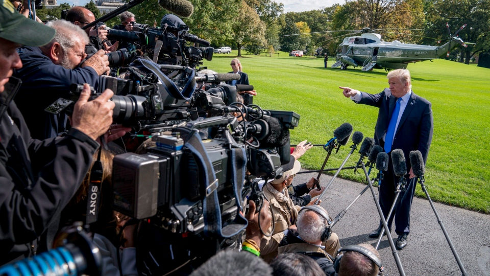 U.S. President Donald Trump calls on a reporter before boarding Marine One on the South Lawn of the White House in Washington on Oct. 25, 2017. (THE CANADIAN PRESS / AP, Andrew Harnik)