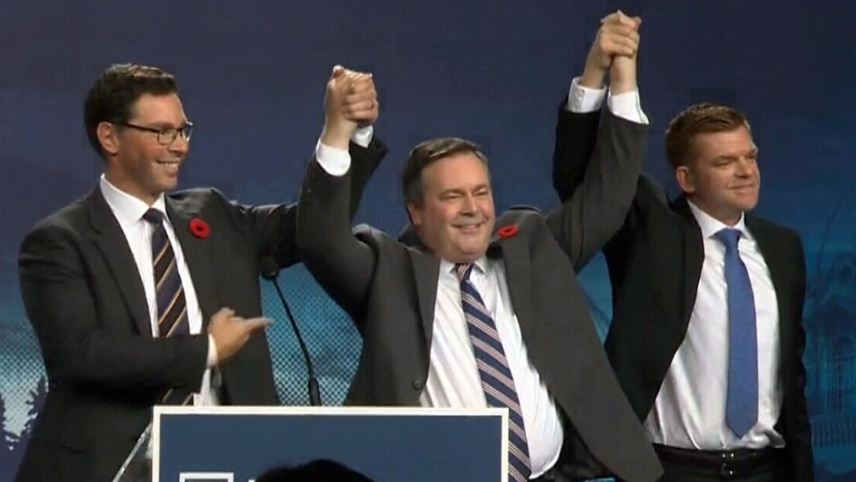 Jason Kenney, centre, celebrates with former Wildrose leader Brian Jean, right, and lawyer Doug Schweitzer, left, after winning the leadership of Alberta's United Conservative Party.