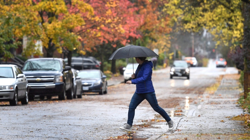 A woman's crosses the street in the rain in Ottawa on Monday, Oct. 30, 2017. (Justin Tang/THE CANADIAN PRESS)