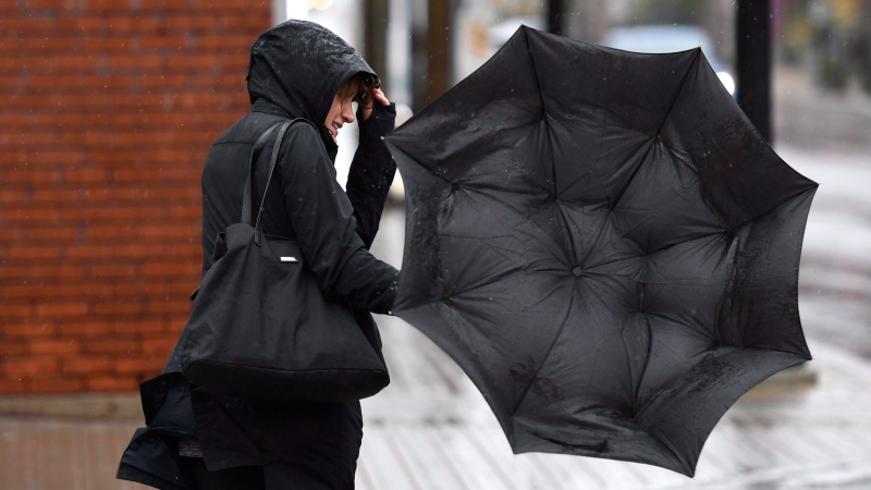 A woman's umbrella flips inside out as she shields herself from the rain and wind in Ottawa on Monday, Oct. 30, 2017. (Justin Tang/THE CANADIAN PRESS)