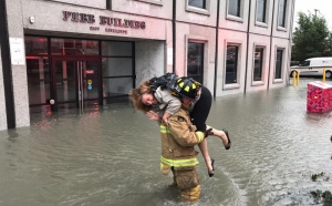 Firefighter carries woman, flooding,