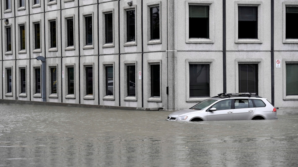 A car sits in the flooded parking lot of the Pebb Building, following a rain storm in Ottawa on Monday, Oct. 30, 2017. (THE CANADIAN PRESS/Justin Tang)