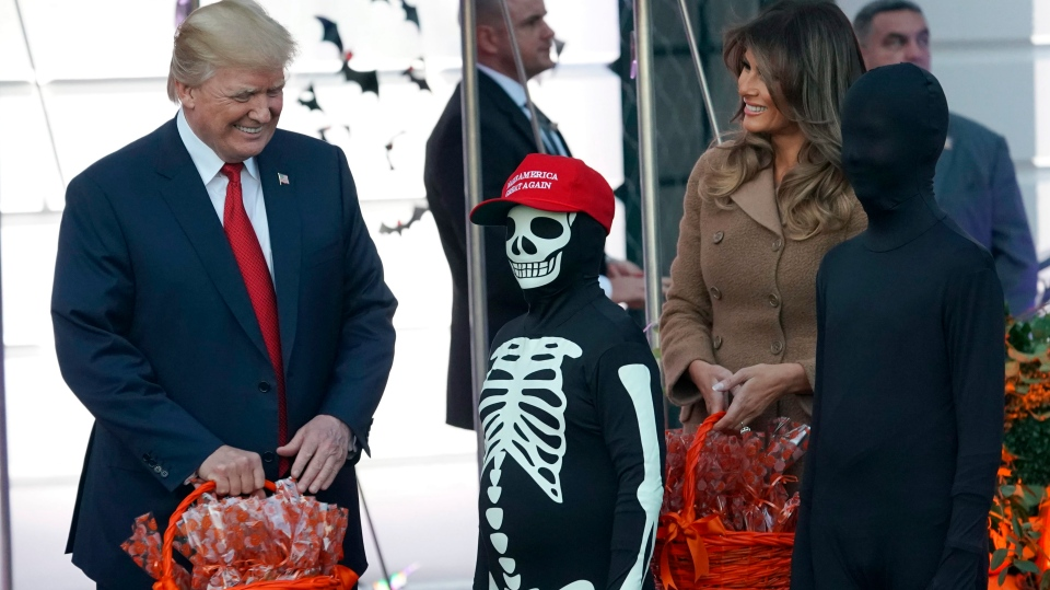 U.S. President Donald Trump and first lady Melania Trump hand out treats as they welcome children from the Washington area and children of military families to trick-or-treat celebrating Halloween at the South Lawn of the White House in Washington, Monday, Oct. 30, 2017. (AP Photo/Pablo Martinez Monsivais)