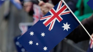 An Australian flag is held in Sydney, Australia, on Thursday, April 25, 2013. (AP / Rick Rycroft)