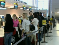 Passengers line up before boarding a flight to Mexico at Pearson International Airport, Tuesday, April, 28, 2009.