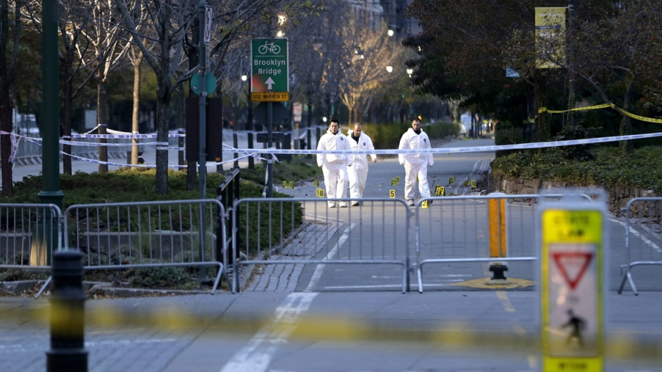 Emergency officials walk near evidence markers on the west side bike path in lower Manhattan, New York, on Nov. 1, 2017. (Seth Wenig / AP)