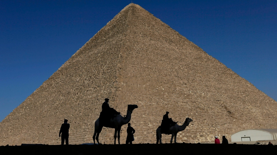 In this Dec. 12, 2012 file photo, policemen are silhouetted against the Great Pyramid in Giza, Egypt. (AP Photo/Hassan Ammar, File)