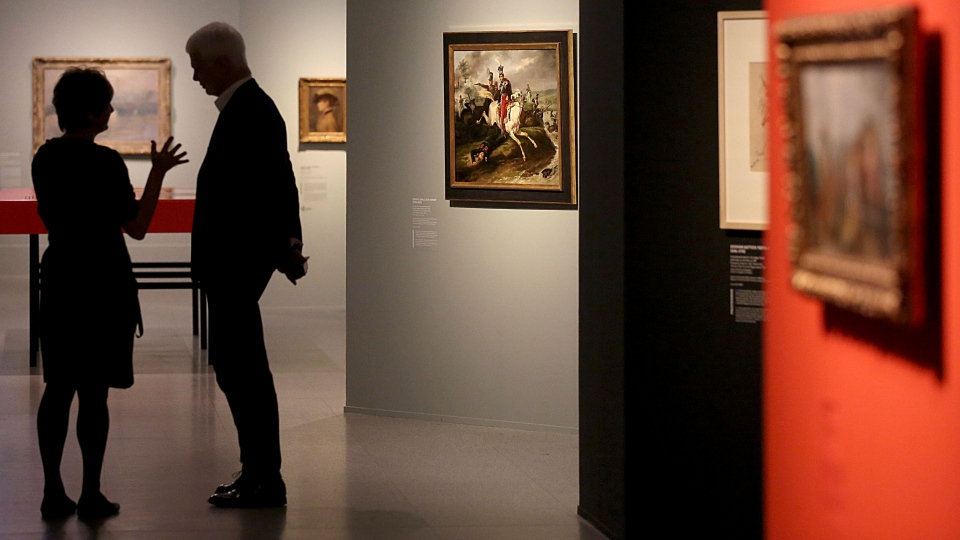 Museum employees walking through the exhibition 'Gurlitt: Status Report' in Bonn, Germany, Thursday, Nov. 2, 2017. Bundeskunsthalle museum is presenting some 250 art works from the 1,500-piece collection hoarded for decades by the late collector Cornelius Gurlitt, including pieces likely looted from Jewish owners under Nazi rule. (Oliver Berg/dpa via AP)
