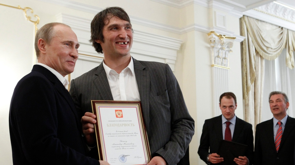 In this May 29, 2012, file photo, Russian national ice hockey team member Alexander Ovechkin, right, holds a certficate of recognition given to him by Russian President Vladimir Putin, left, in the Novo-Ogaryovo residence outside Moscow. (AP / Sergei Karpukhin, Pool)
