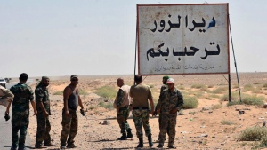 """This file photo released Sept. 3, 2017, by the Syrian official news agency SANA, shows Syrian troops and pro-government gunmen standing next to a sign in Arabic which reads, """"Deir el-Zour welcomes you,"""" in the eastern city of Deir el-Zour, Syria. (SANA via AP, File)"""