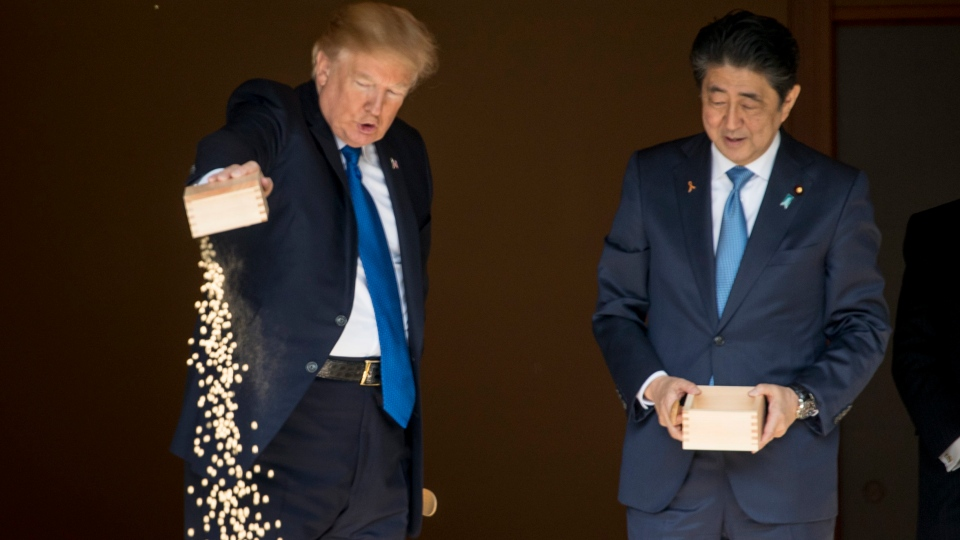 U.S. President Donald Trump pours the remainder of his fish food out as he and Japanese Prime Minister Shinzo Abe feed fish in a koi pond at the Akasaka Palace, Monday, Nov. 6, 2017, in Tokyo. Trump is on a five country trip through Asia traveling to Japan, South Korea, China, Vietnam and the Philippines. (AP Photo/Andrew Harnik)