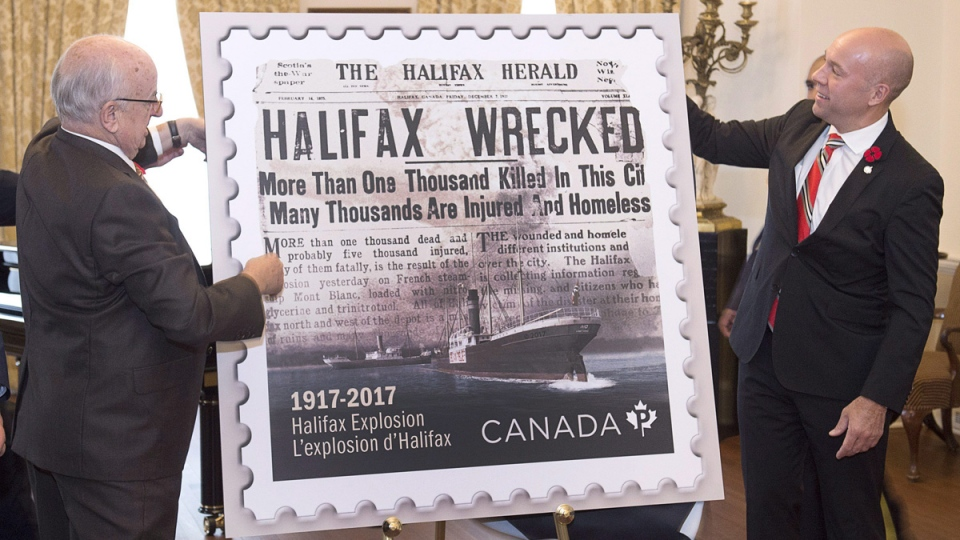 Nova Scotia Lt.-Gov. Arthur J. LeBlanc, left, and Andy Fillmore, MP for the federal riding of Halifax, unveil the Canada Post Halifax Explosion commemorative stamp in Halifax on Nov. 6, 2017. (Andrew Vaughan / THE CANADIAN PRESS)