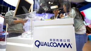 FILE - In this Thursday, April 27, 2017, file photo, visitors look at a display booth for Qualcomm at the Global Mobile Internet Conference (GMIC) in Beijing. Broadcom is making an unsolicited, $130-billion offer for rival chipmaker Qualcomm, the largest deal ever in the tech industry that will face intense regulatory scrutiny. (File/AP Photo)