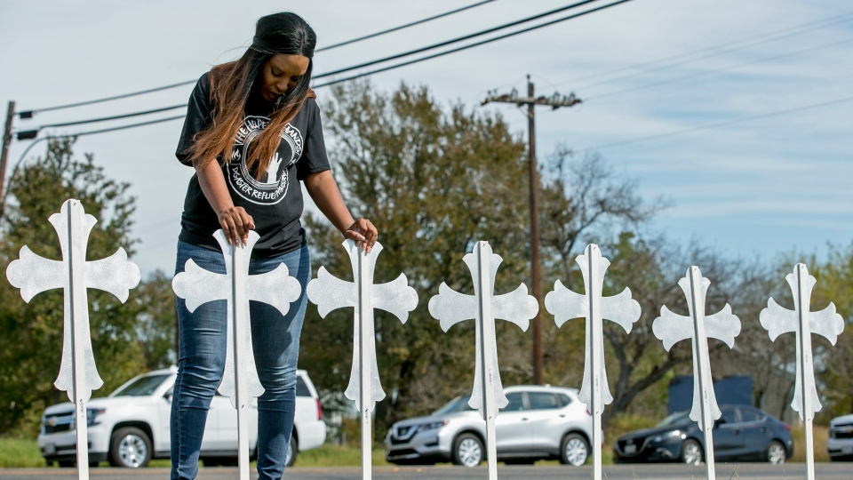 Sheree Rumph of San Antonio prays over two of the 26 crosses erected in memory of the 26 people killed in a shooting in Sutherland Springs, Texas on Monday, Nov. 6, 2017. (Jay Janner/Austin American-Statesman via AP)