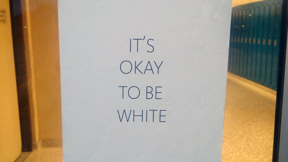 Signs reading 'It's okay to be white' were posted outside two Kitchener high schools.