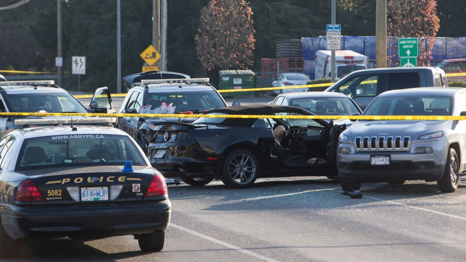 Police officers investigate the scene of a shooting that left one Abbostford Police officer dead in Abbotsford, B.C., on Monday, Nov. 6, 2017. (THE CANADIAN PRESS/Ben Nelms)