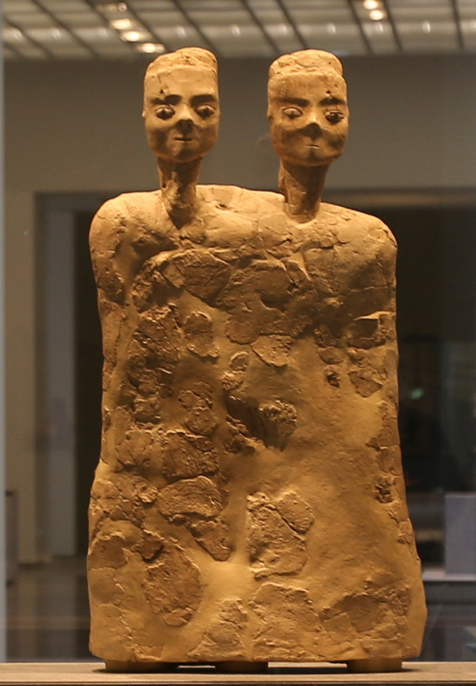 """In this Monday, Nov. 6, 2017 photo, """"Monumental Statue with two heads"""" from Jordan about 6500 BCE, is displayed at the new Louvre Museum in Abu Dhabi, United Arab Emirates. (AP Photo/Kamran Jebreili)"""