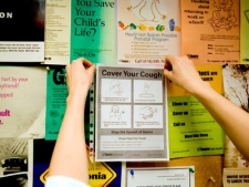 A nurse posts a medical advisory in the waiting room of a Toronto health clinic to help curb the spread of swine flu on Thursday, April 30, 2009. (Darren Calabrese / THE CANADIAN PRESS)