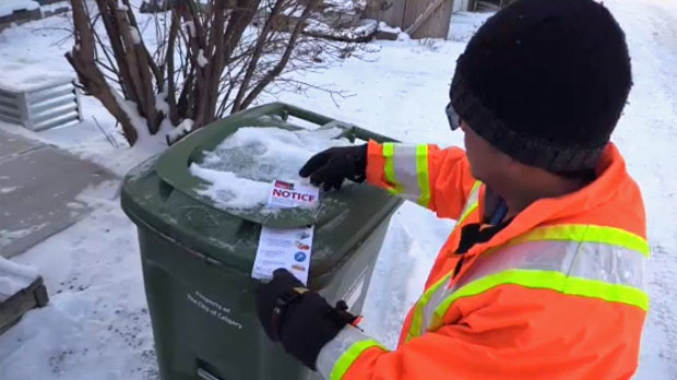 A City of Calgary worker leaves a tag on a green cart notifying the owner of an unacceptable item in the bin