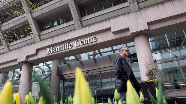 A man walks by the Manulife Centre in Toronto the day of the Manulife Financial Annual General Meeting on May 3, 2012. (THE CANADIAN PRESS/Aaron Vincent Elkaim)