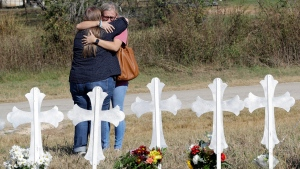 Two women hug at a makeshift memorial for the First Baptist Church shooting victims, in Sutherland Springs, Texas, on Tuesday, Nov. 7, 2017. (AP Photo/David J. Phillip)
