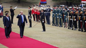 U.S. President Donald Trump, right on red carpet, walks with South Korea's President Moon Jae-in at the Presidential Blue House in Seoul, on Nov. 7, 2017. (Kim Hong-ji / Pool Photo via AP)