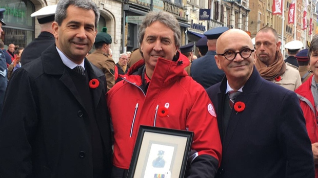 Bill Haber is seen with a photo of Pte. McKinnon in Ypres, Belgium on Nov. 11, 2017. (Bill Haber)