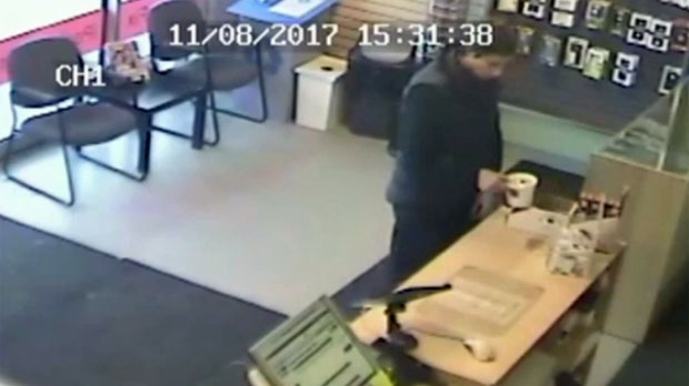 Surveillance camera still of the emptying of the cash container of a poppy box at a store on Macleod Trail on November 8 (courtesy: Cell Phone Repair)