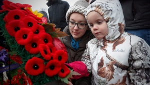 Isolde Chisholm pins her poppy to a wreath with the help of her aunt Rosemund Ragetli at a cenotaph during a Remembrance Day service in Winnipeg, Saturday, November 11, 2017. (John Woods / The Canadian Press)