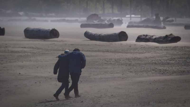 High winds whip up sand as a couple walks along Spanish Banks Beach in Vancouver, B.C., on Monday April 29, 2013. THE CANADIAN PRESS/Darryl Dyck