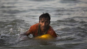 Rohingya Muslim Abdul Karim, 19, uses a yellow plastic oil container as a flotation device as he swims the Naf river while crossing the Myanmar-Bangladesh border in Shah Porir Dwip, Bangladesh on Nov. 4, 2017. (AP / Bernat Armangue)