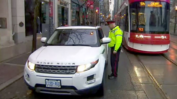Toronto police Const. Clint Stibbe warns a driver about the newly implemented rules on a downtown portion of King Street on Nov. 13, 2017.