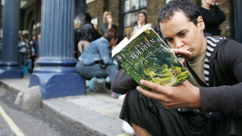 A hopeful man reads a 'Lord of the Rings' book as he joins hundreds of people queuing outside the Theatre Royal Drury Lane in London Monday, Sept. 18, 2006. (AP Photo/Sang Tan)