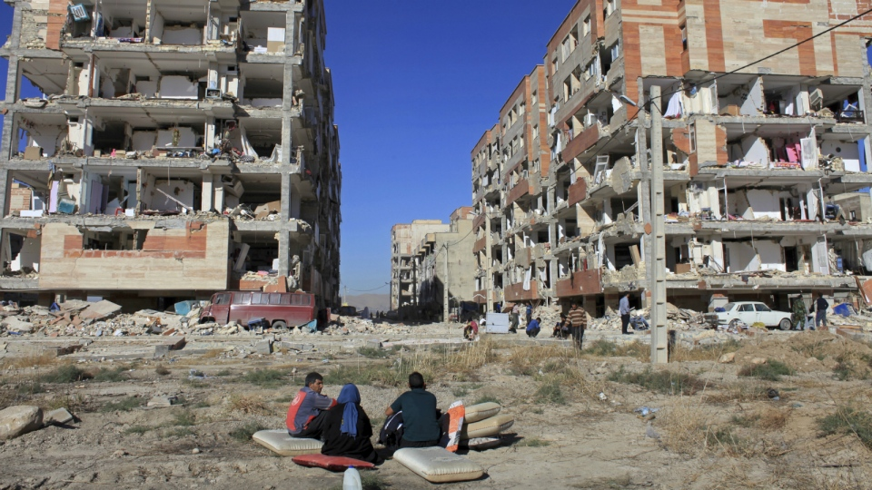 Survivors sit in front of buildings damaged by an earthquake, in Sarpol-e-Zahab, western Iran, Monday, Nov. 13, 2017. (AP / Omid Salehi)