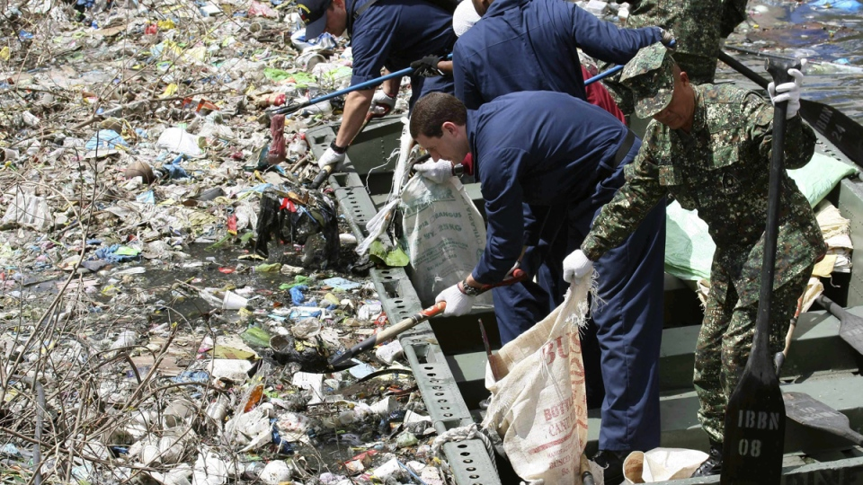 U.S. Navy crewmen and their Philippine counterparts scoop up dirt and other garbage in a river during a clean up effort along a canal in Manila, Philippines, on Sept. 6, 2010. (Bullit Marquez / AP)