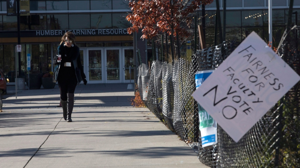 A woman walks down a quiet pathway at a Humber College campus in Toronto as Faculty members maintain their strike on Wednesday November 8, 2017. The chair of the Ontario colleges' bargaining team is repeating the call for the Ontario Public Service Employees Union to suspend the strike in the lead-up to a vote on the latest contract offer. THE CANADIAN PRESS/Chris Young