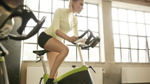 A woman is pictured on a spin bike. (Jacob Ammentorp Lund / Istock.com)