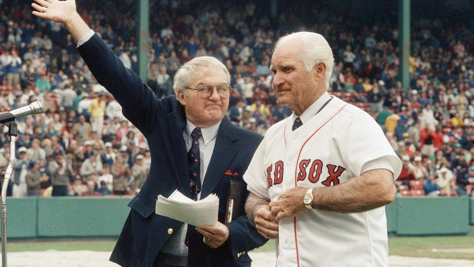 In this May 21, 1988, file photo, the radio voice of the Boston Red Sox, Kent Coleman, left, presents former Red Sox second baseman Bobby Doerr to the crowd at Fenway Park during a ceremony to retire his number 1. (AP / Carol Francavilla, File)
