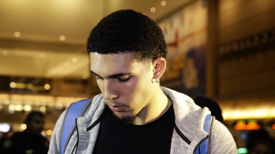 UCLA basketball player LiAngelo Ball keeps his head down as he leaves Los Angeles International Airport in Los Angeles on Tuesday, Nov. 14, 2017. (AP / Jae C. Hong)