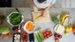 A woman prepares a vegetarian meal. (andresr / Istock.com)