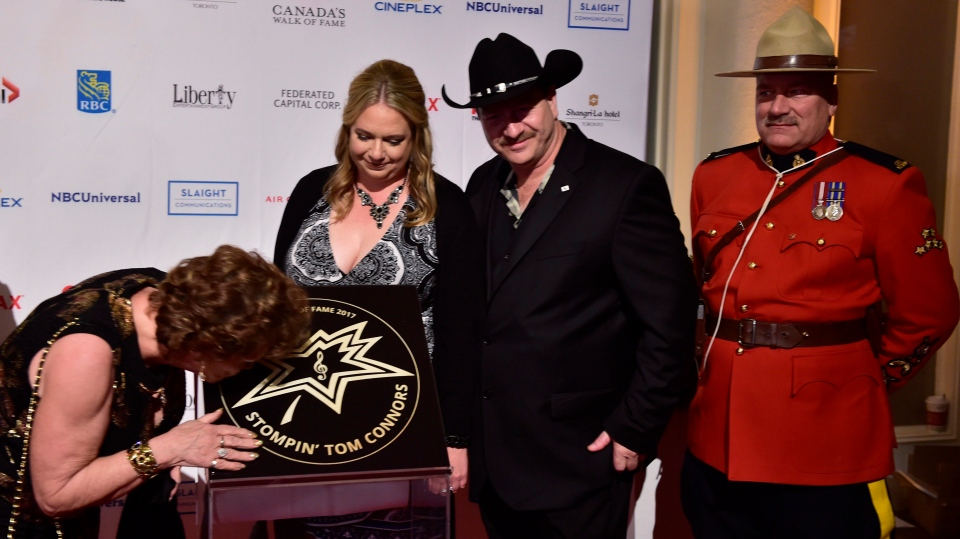 Lena Connors (left), the widow of Stompin' Tom Connors, kisses the late country singer's star as Jessica Roselle, Stompin Tom Connors Jr.'s wife and Taw Connors (right) look on at as the late country singer's star is unveiled at the Walk of Fame induction ceremony in Toronto, Wednesday, Nov.15, 2017. (THE CANADIAN PRESS/Frank Gunn)